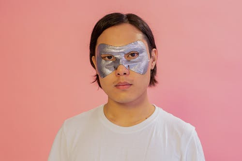 Serious Asian male with moisturizing mask on eyes looking at camera on pink background during skincare procedure in light studio