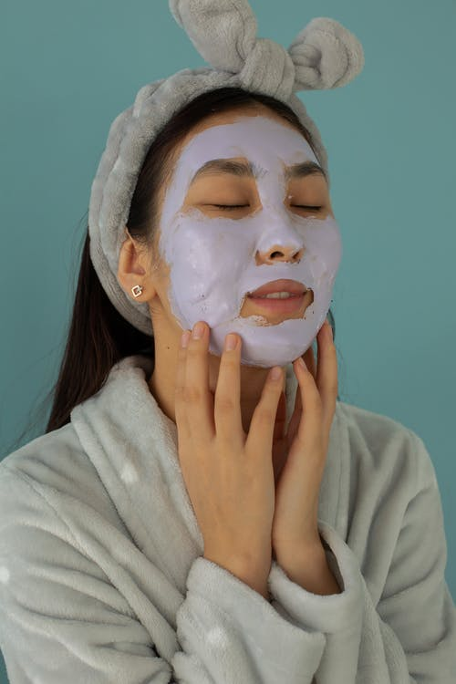 Tranquil female with closed eyes and facial mask wearing bathrobe while standing on blue background during beauty procedure in studio