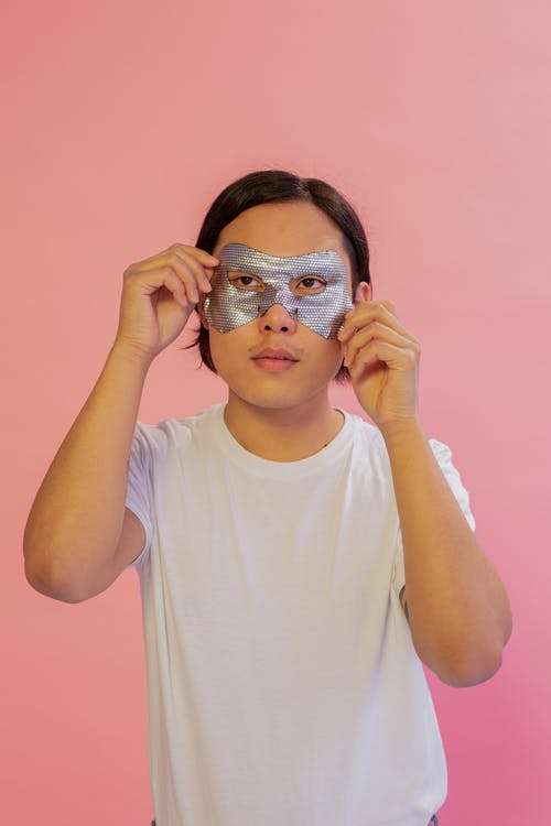 Calm Asian man looking away while applying moisturizing eye mask on pink background in light studio during daily beauty routine