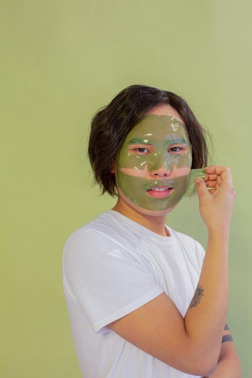 Content Asian man applying facial mask in studio