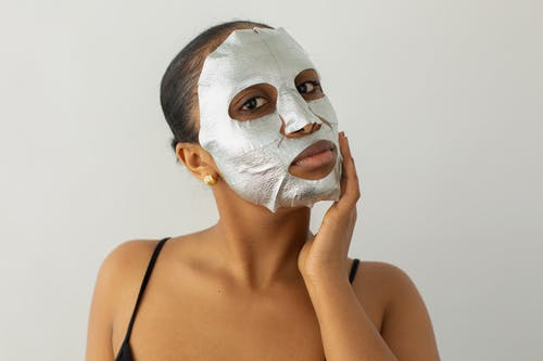 Young African American female touching face with hydrating mask while looking at camera on light background