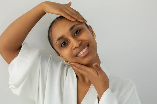 Smiling Indian woman touching face with pure skin