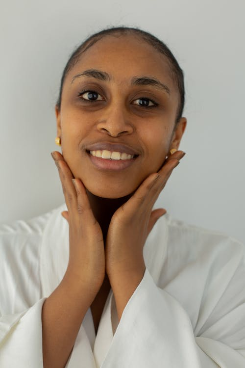Smiling young Indian female in robe touching face while looking at camera on light background