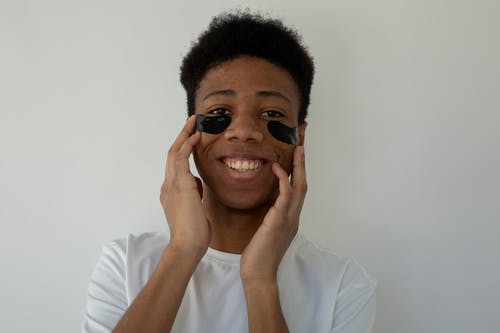 Cheerful black teenager touching face with eye patches