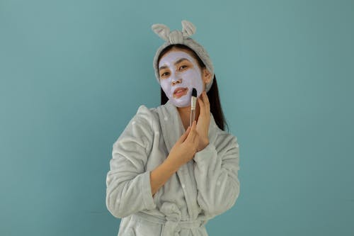Young ethnic female in robe and headband applying cleansing mask with cosmetic brush while looking at camera on turquoise background