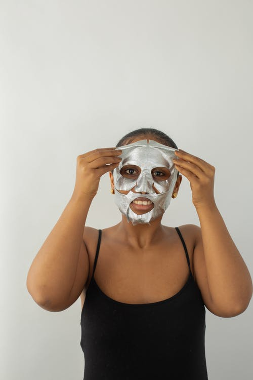 Black woman removing hydrating mask from face