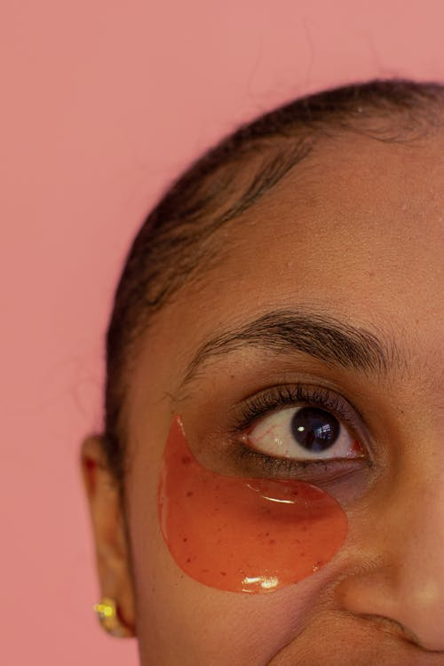 Crop unrecognizable African American female model with eye patch on face standing on pink background during skincare procedure in studio