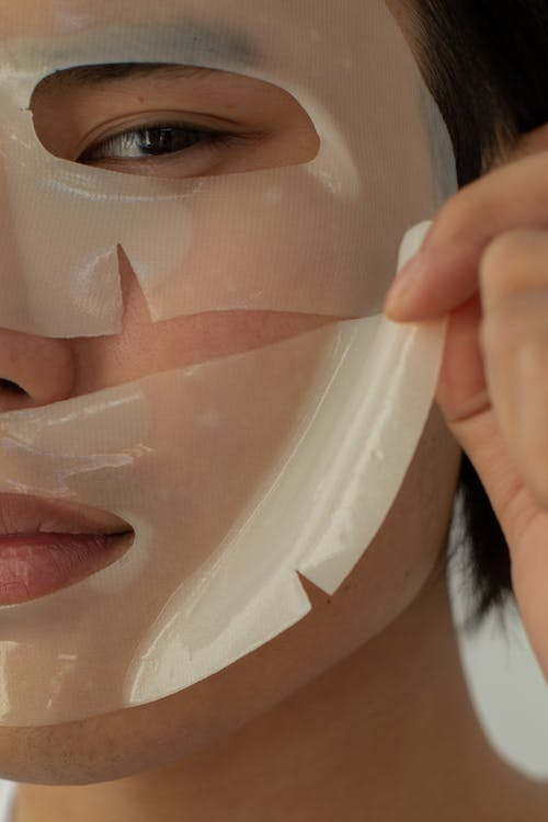 Crop unrecognizable Asian male model looking at camera while taking off moisturizing facial mask during skincare routine in light studio