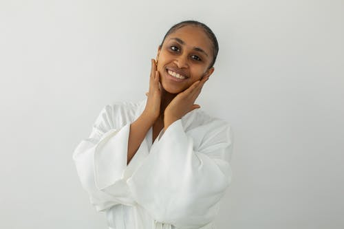 Joyful black woman touching face after beauty procedure