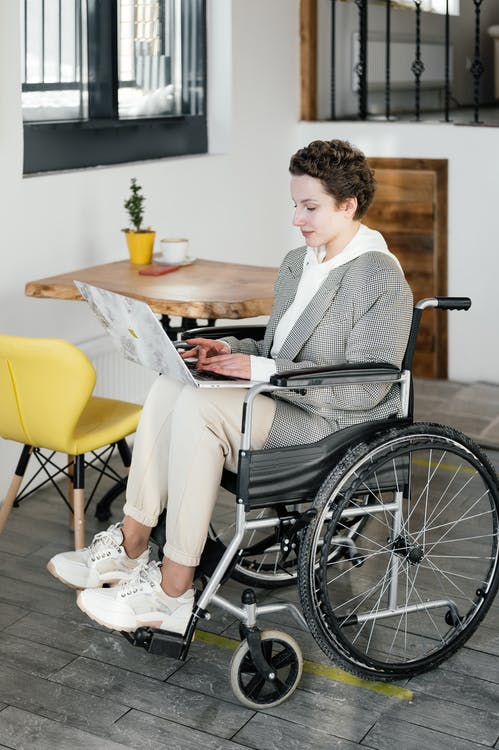 Serious disabled woman working on laptop
