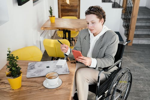 High angle of focused female in wheelchair browsing cellphone at table with netbook and cup of latte