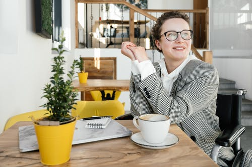 Smiling disabled female remote worker at table in coffee shop