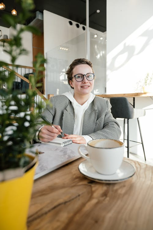 Positive female in stylish eyeglasses taking notes in notepad while sitting at table with laptop and cup of coffee