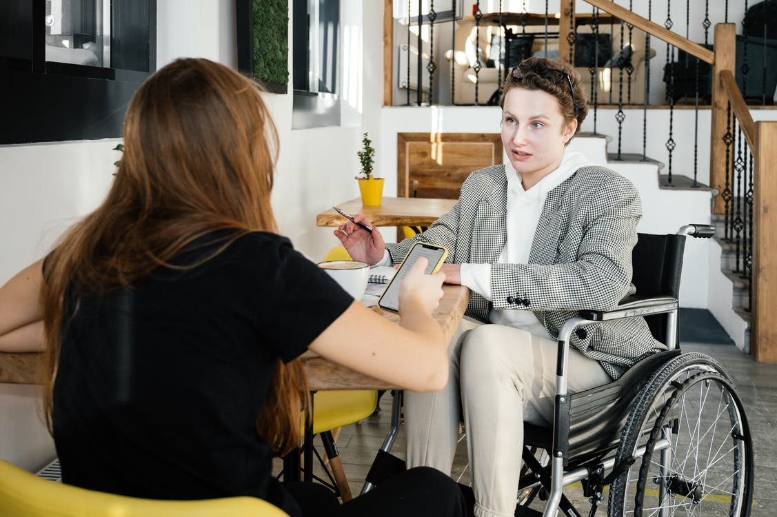 Concentrated female using wheelchair talking to coworker during coffee break in modern cafeteria