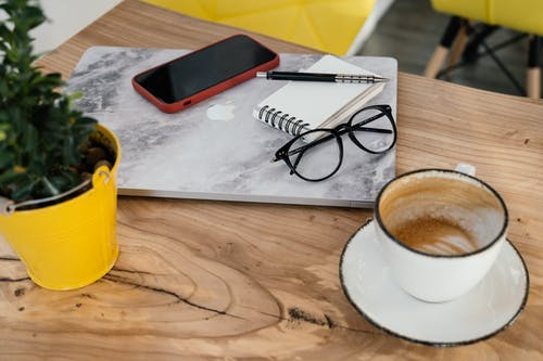 High angle contemporary laptop and smartphone placed on table near cup of half finished cappuccino and copybook in cafeteria