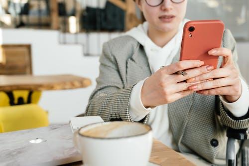 Crop focused female in formal wear and eyeglasses browsing mobile phone while having coffee in cafeteria