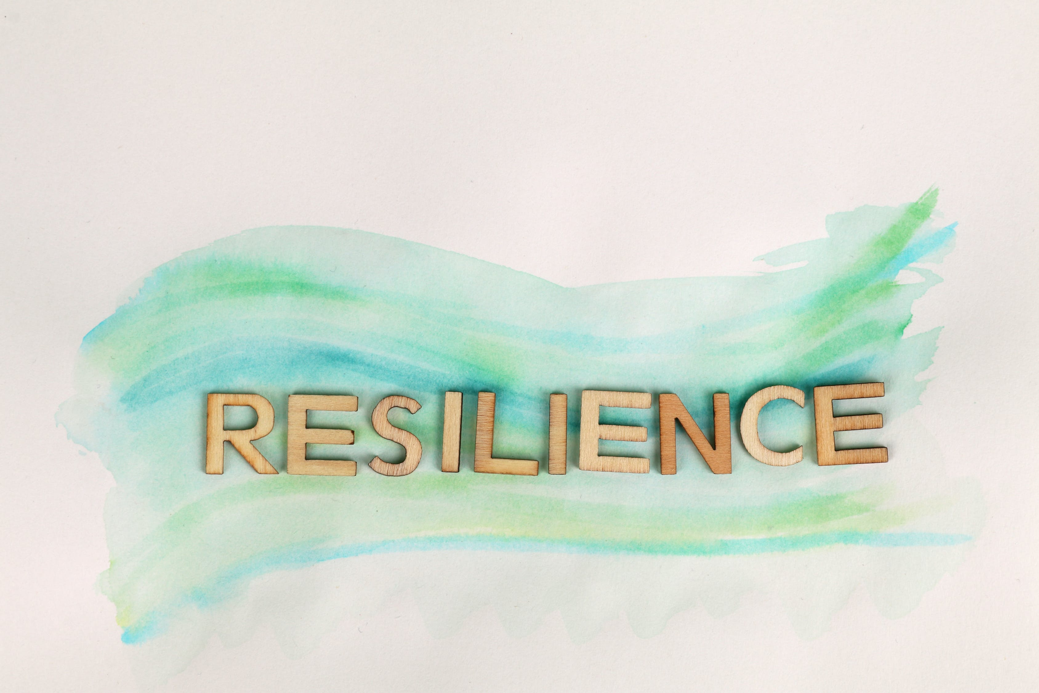 The word 'RESILIENCE' in wood letters on a paper background painted with blue watercolor. Photo used courtesy of pexels.com.