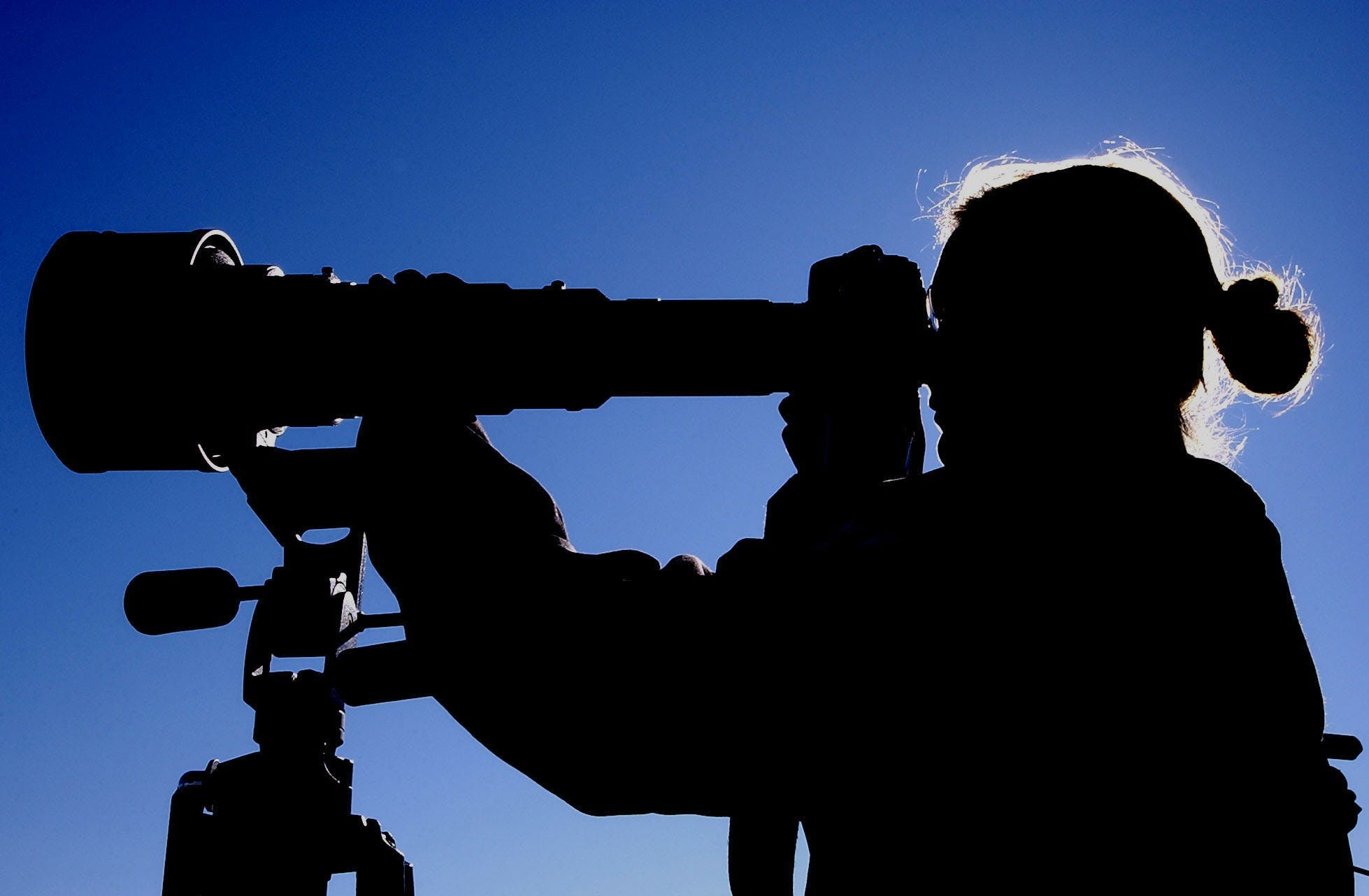 Man Looking at Telescope during Daytime