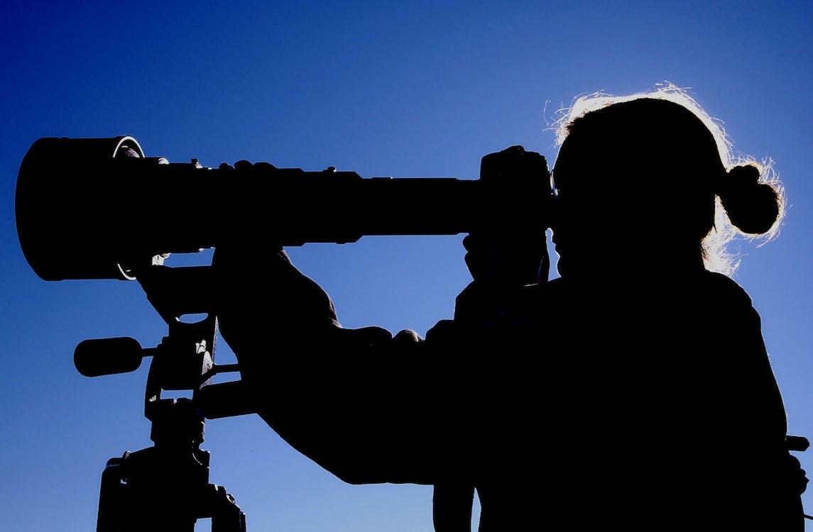 Man Looking at Telescope during Daytime