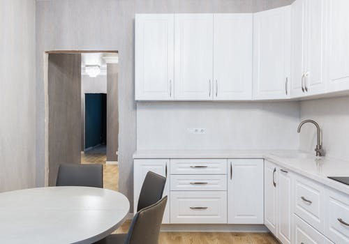 Modern kitchen interior with cabinets against table at home