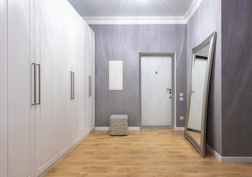 Modern hall interior with entrance door between closet and rectangular shaped mirror on wooden floor at home