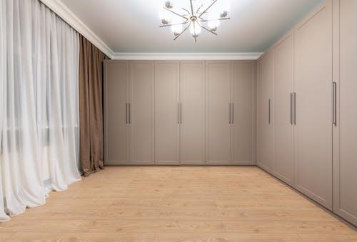Closet on parquet under shiny chandelier at home