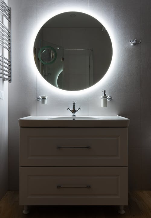 Modern bathroom with washbasin and dispenser bottle under round shaped mirror on light wall in house