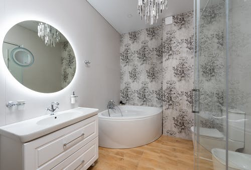 Creative design of bathroom with toilet bowl and small bath against mirror above washbasin and cabinet at home
