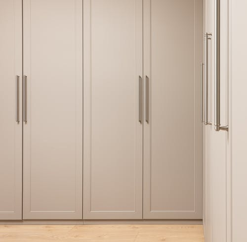 Contemporary closet with beige doors and metal handles above floor in modern light house