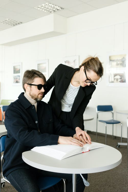 Woman Helping a Man Sitting on a Chair