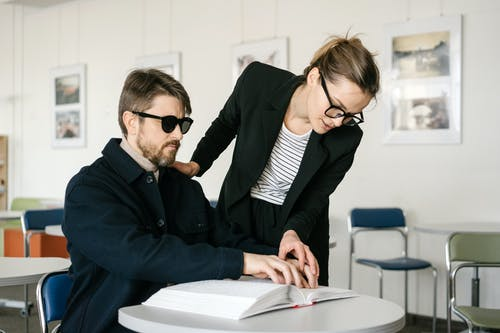 Woman Assisting a Blind Man