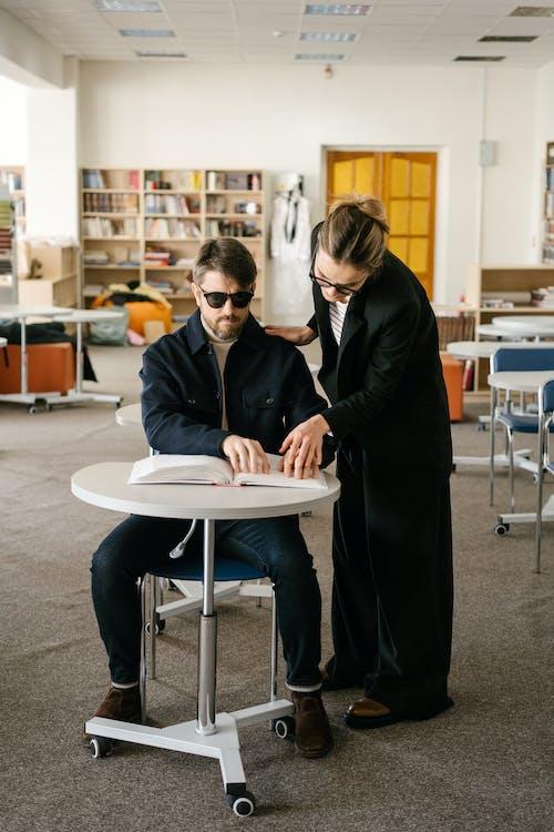 Woman in Black Long Sleeve Shirt Helping a Man