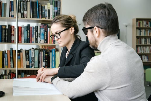 Woman Placing Man's Hand on a Book