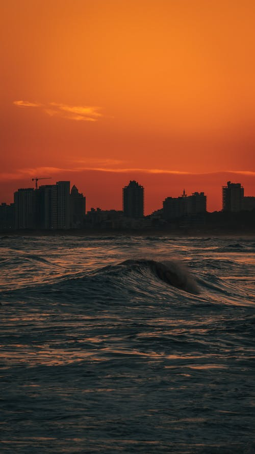 Sea Waves Near City Buildings during Sunset