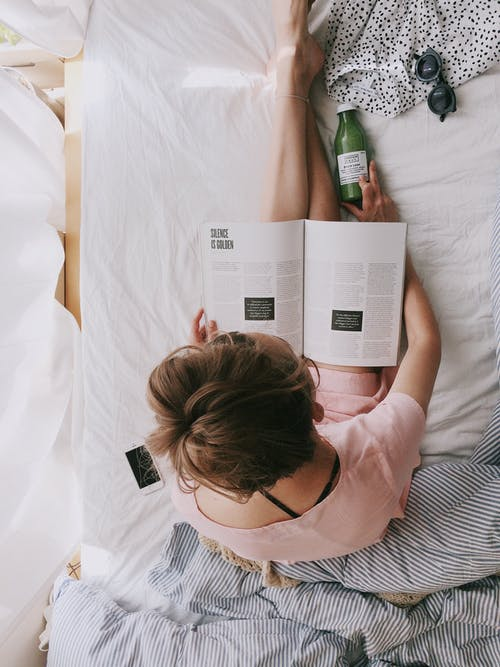 Woman in Pink Dress Sitting on Bed While Reading