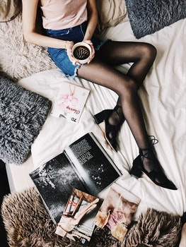 Flatlay Photography of a Woman Holding White Mug With Black Liquid While Lying on a Bed Surrounded by Fur Pillows and Magazines