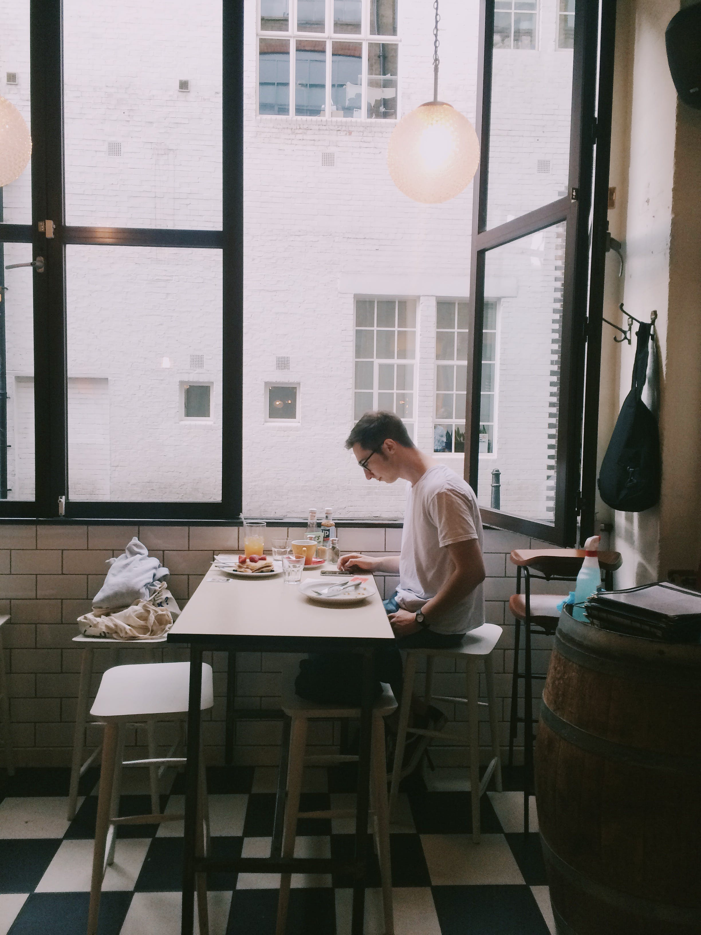 Man Sitting in Front of Table Holding Smartphone Beside Window