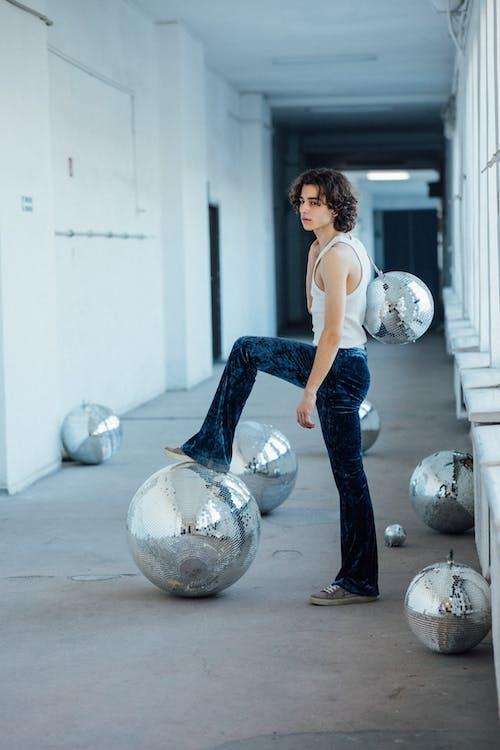 A Caucasian Man Stepping on a Disco ball