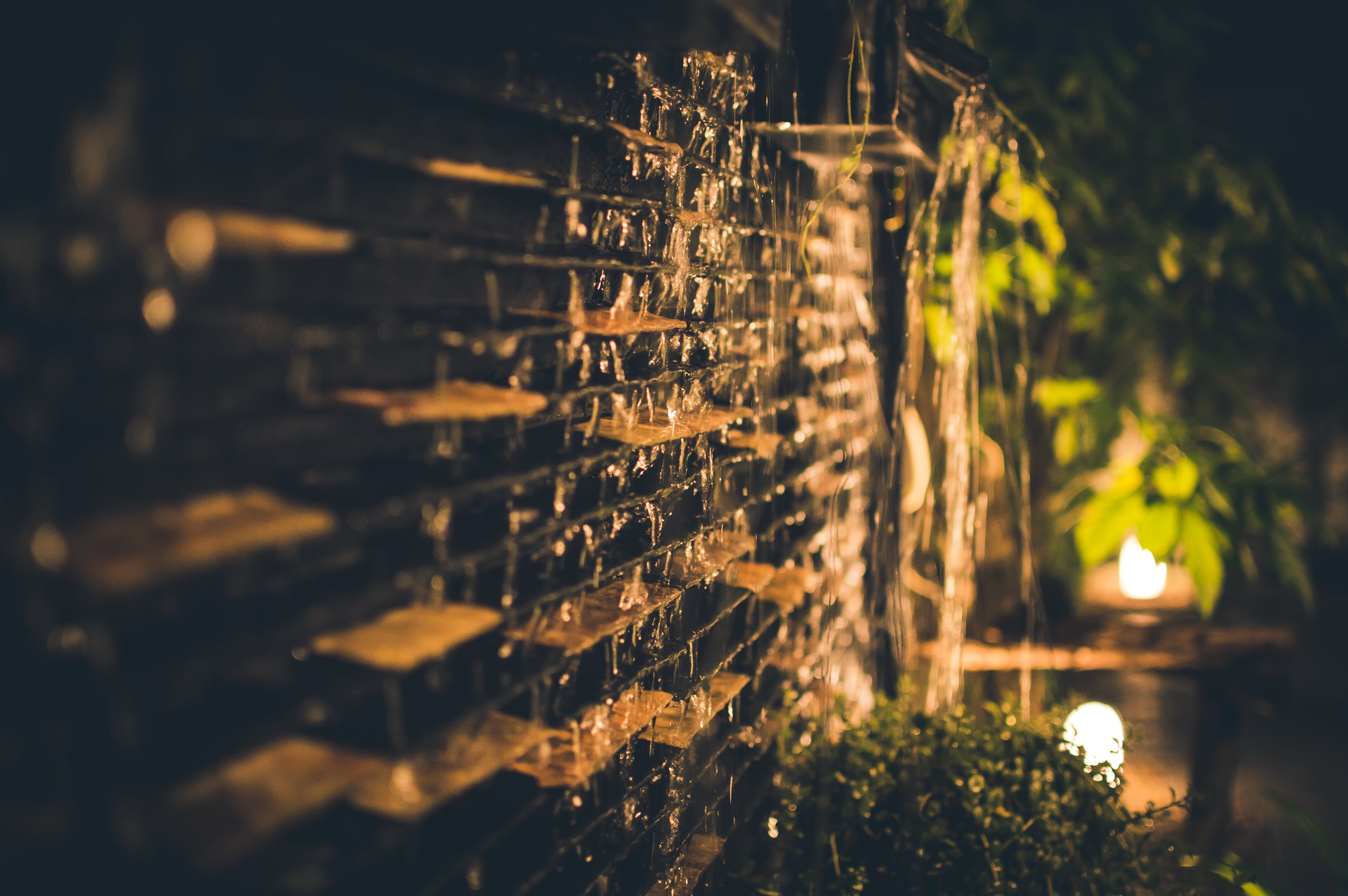 Selective Focus Photography of Brown Brick Wall during Nighttime