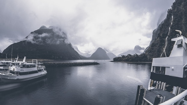 Grayscale Photo of Yachts on Body of Water Under Cloudy Sky