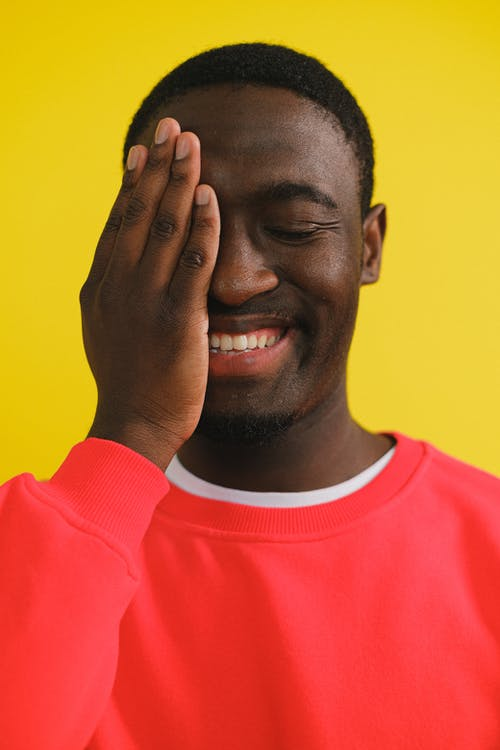 Joyful African American male in red sweater covering half face with hand and standing with eye closed on yellow background