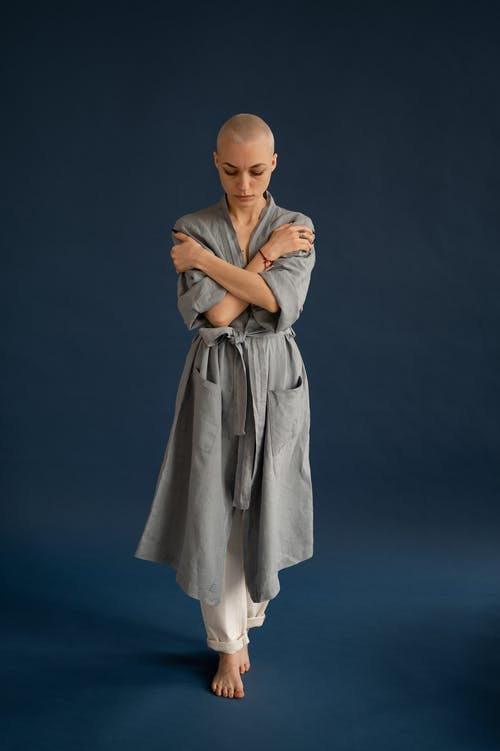 Wistful bald woman in robe embracing self in studio