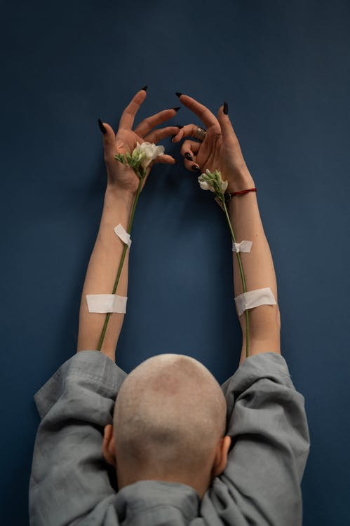 Back view of anonymous female patient with blossoming flowers and medical patches representing dropper concept during cancer treatment on blue background