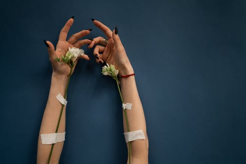 Crop anonymous female patient with blossoming flowers and medical patches for dropping medical liquid during therapy