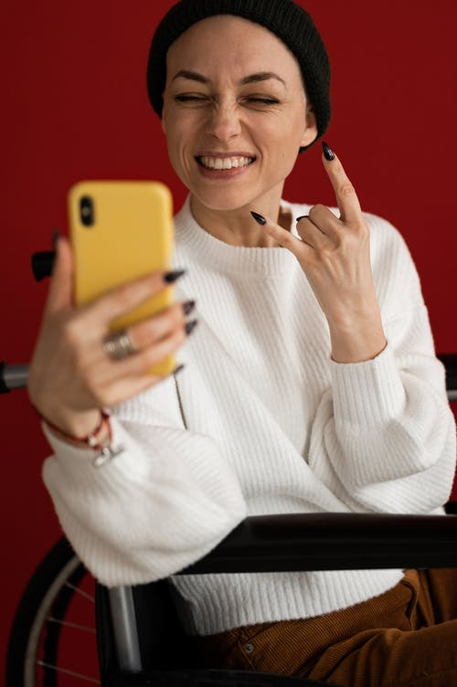 Crop optimistic female patient in casual clothes and hat smiling and showing sign of horns while having video call via smartphone sitting in wheelchair against red background
