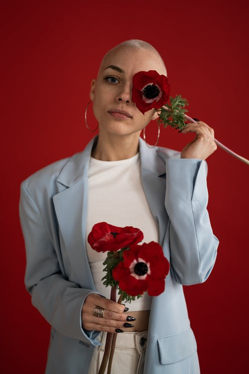Confident female covering face with red poppy