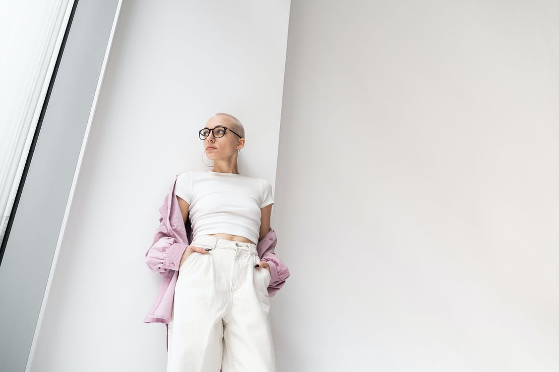 Fashionable woman in light room near wall