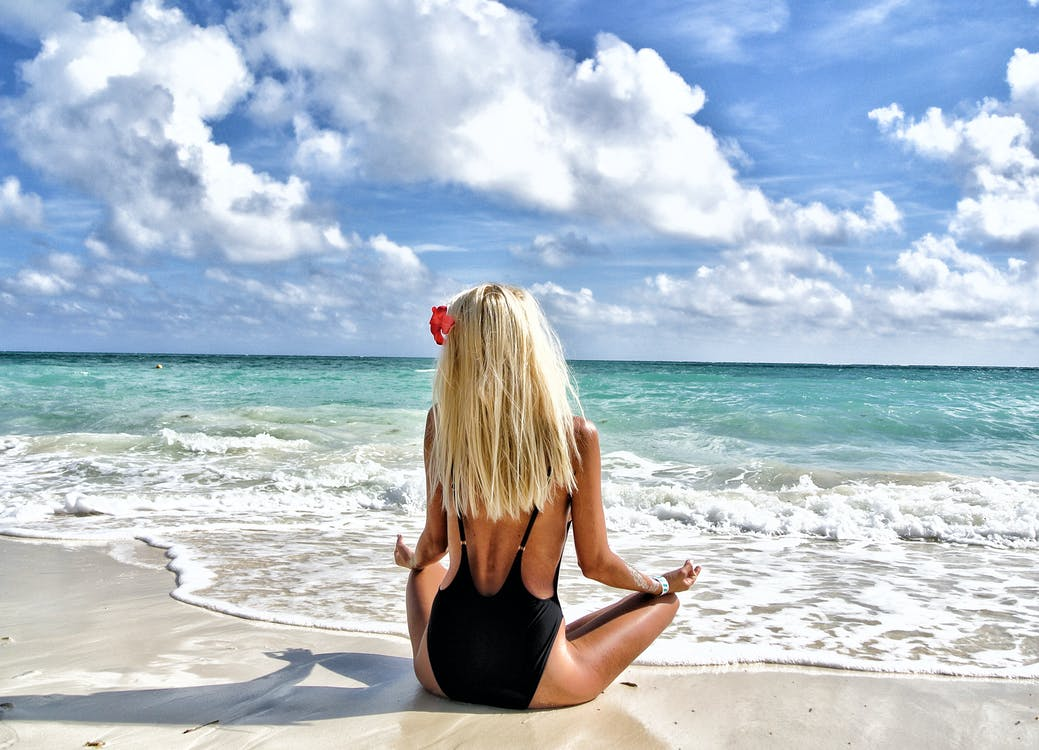 Woman Wearing Black Monokini Meditating on in Front of Sea Under Blue and White Sky