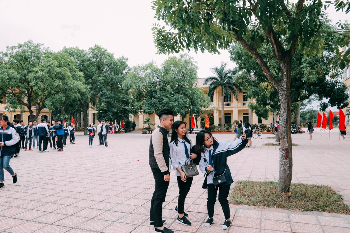 Photo of Two Women Beside Man Taking a Picture