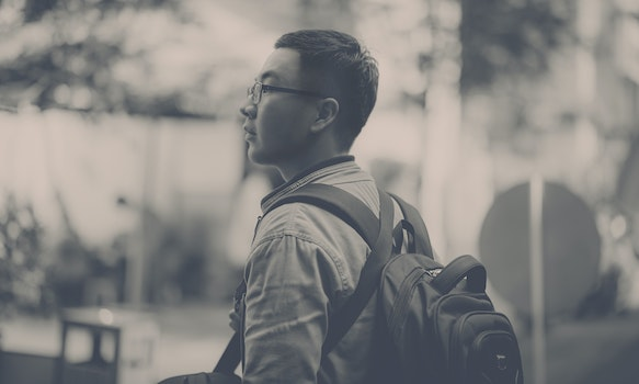 Grayscale Photo of Man Wearing Backpack